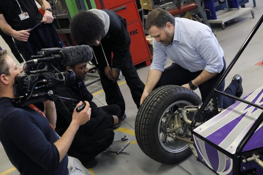 Cameraman filming Sion Simon speaking to an Automotive student