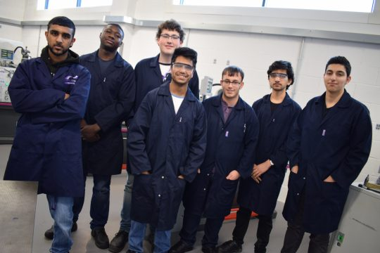 Group of male engineering students in their overalls