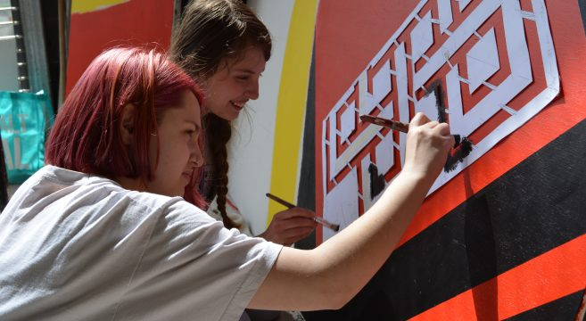 Two art students preparing a mural