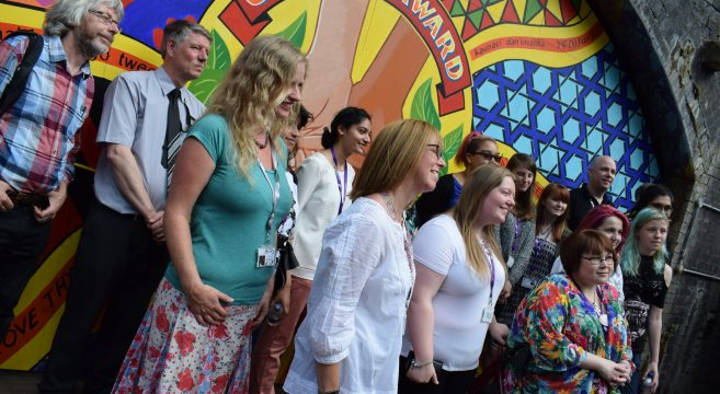 Group of students and staff member pictured in front of a mural