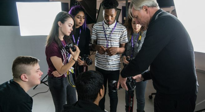 Photography teacher showing students a professional camera