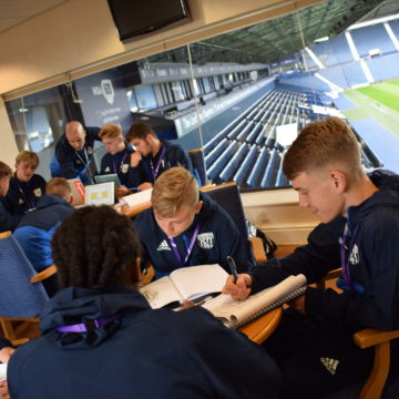 Male Sport students making notes at a table