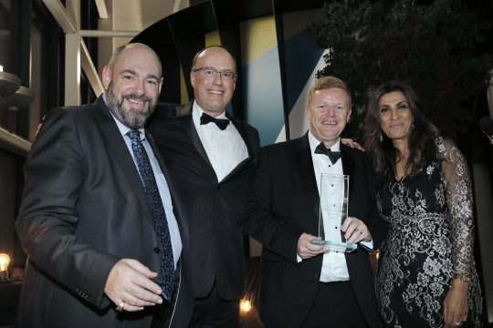 A group of representatives from MiGlass holding the Business Innovation Award