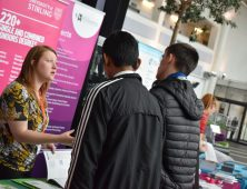 Female representative of Stirling University speaking to two male students