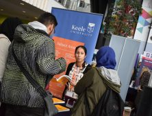 Group of students speaking to a representative of Keele University