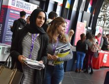 Two female students carrying university prospectus brochures