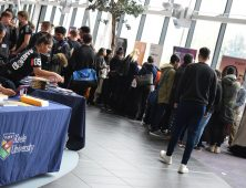 Large groups of students speaking to different university representatives