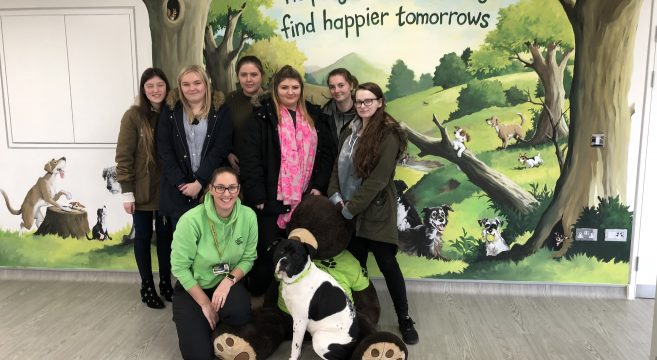 Group of students pictured with dog and Dogs Home staff member
