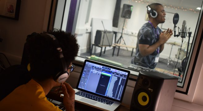 Student singing in recording studio whilst another student listens in on his headphones