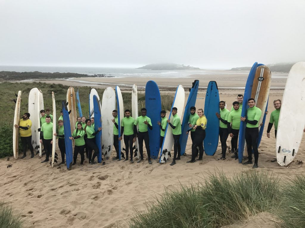 Students pictured on a beach with surfboards