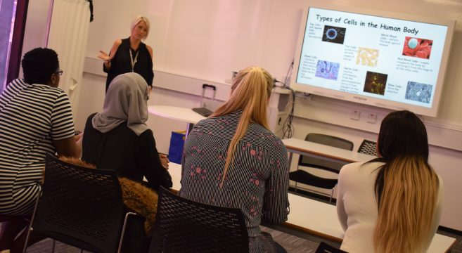 Health and Social Care lectuer speaking to class of female adult students