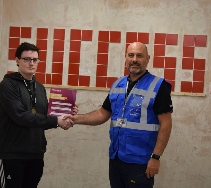 Construction student receiving certificate from teacher