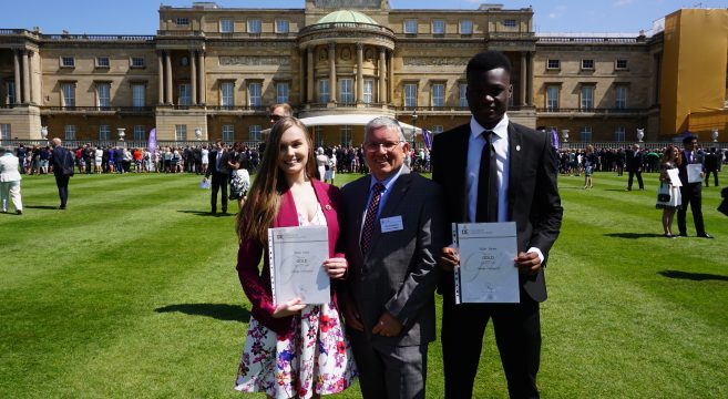 Two students pictured with their Duke of Edinburgh Gold award certificate and a member of staff