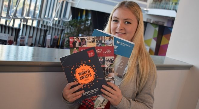 Student with university prospectuses