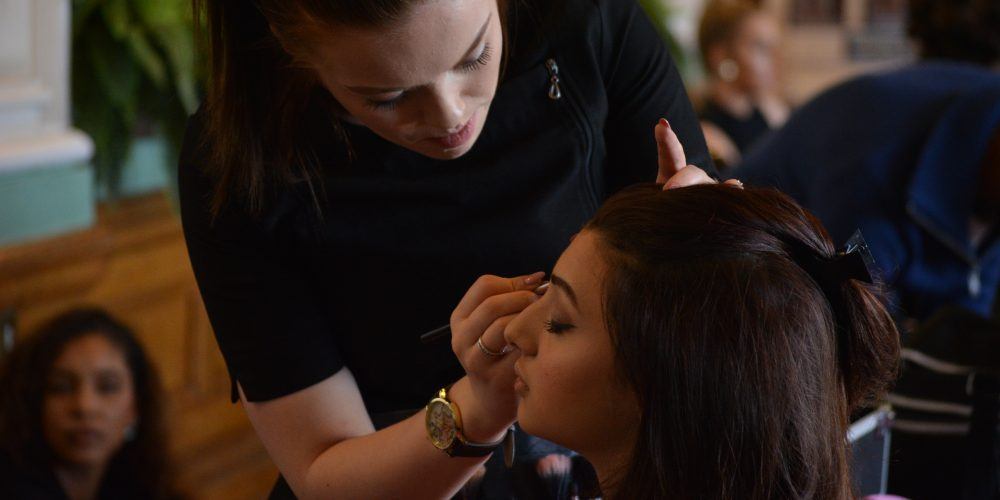Student applying makeup to a customer