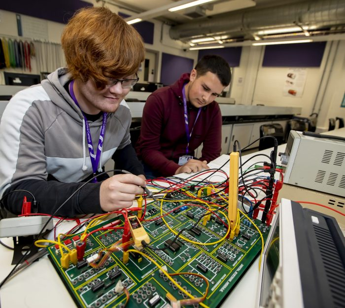 Two engineering students working on an electrical installation