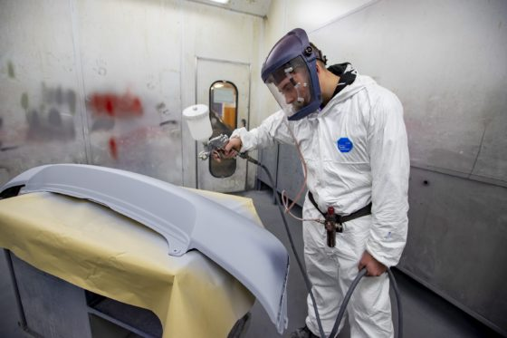 Student wearing protective equipment using paint and spray machine