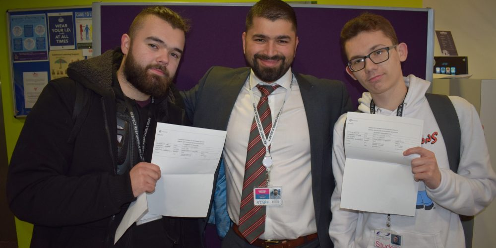Teacher with two students showing their GCSE results