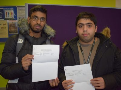Two male students showing their GCSE results