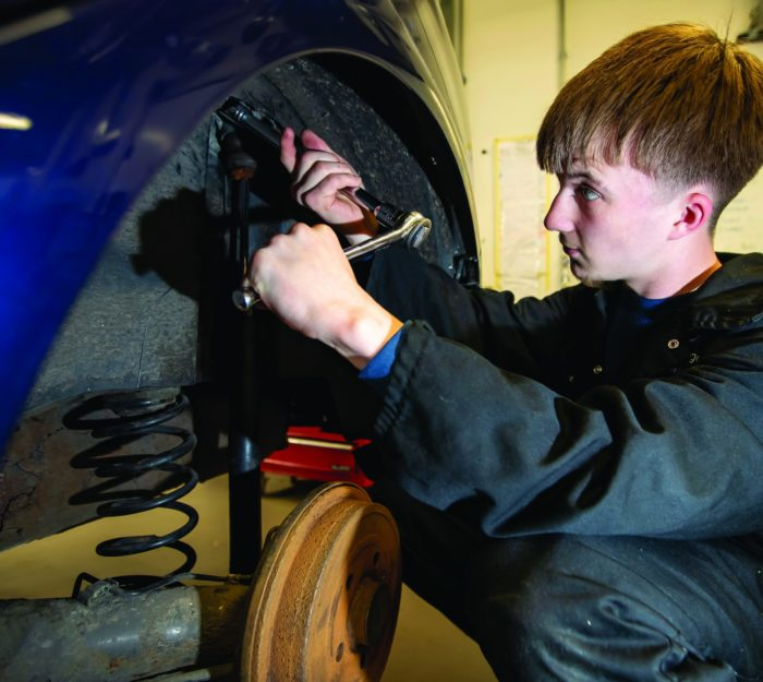 Automotive Student working on the wheel of a car