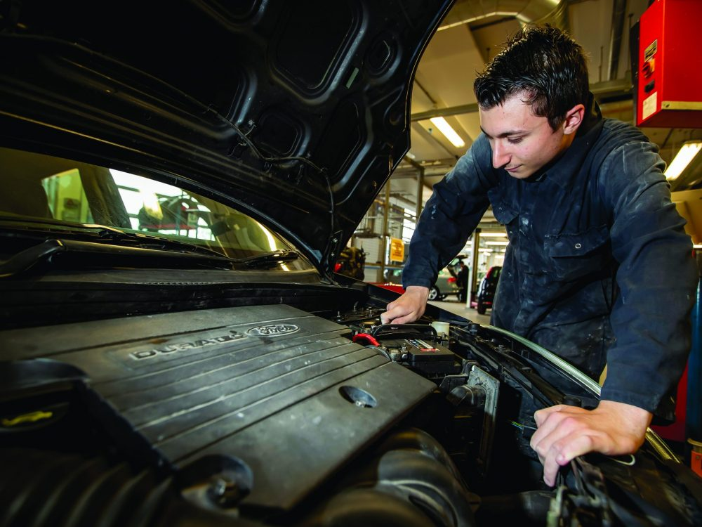 Automotive student under the hood of a car