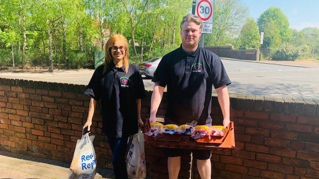 Two lecturers carrying food as part of outreach programme
