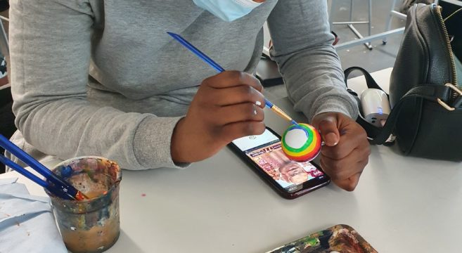 Student painting a Christmas bauble