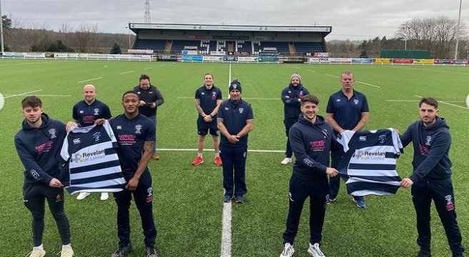 Four students on rugby pitch holding their new first team shirts