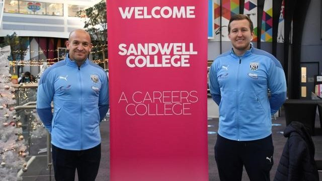 Scott Thomas and a member of the Albion Foundation next to the college welcome banner