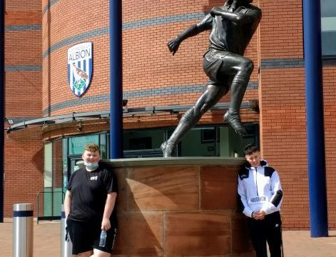 Two students next to statue outside WBA FC