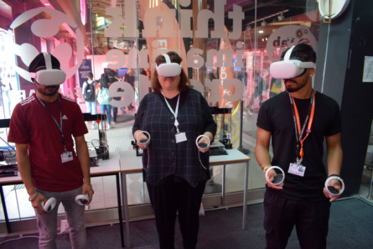 Students and DfE director wearing VR headsets