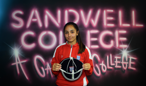 Sport student holding her England cap in front of Sandwell College mural